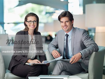 Portrait of smiling businessman and businesswoman working in lobby Stock Photo - Premium Royalty-Free, Image code: 635-06192030