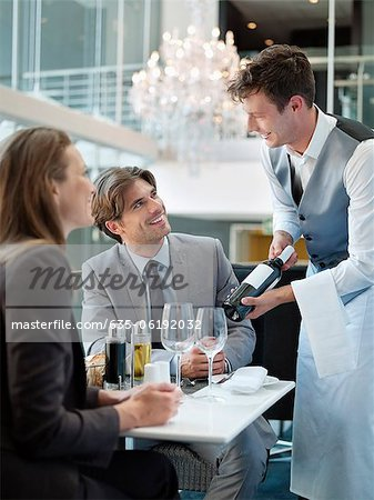 Sommelier presenting wine bottle to couple in restaurant Stock Photo - Premium Royalty-Free, Image code: 635-06192032