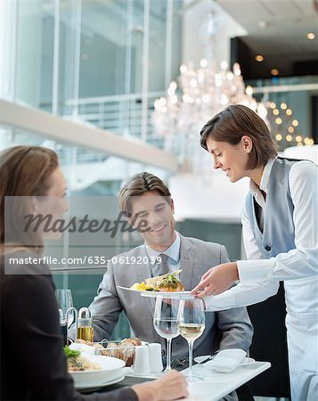 Waitress serving food to couple in restaurant Stock Photo - Premium Royalty-Free, Image code: 635-06192039