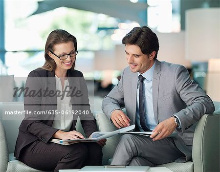 Businessman and businesswoman working in lobby Stock Photo - Premium Royalty-Free, Image code: 635-06192040