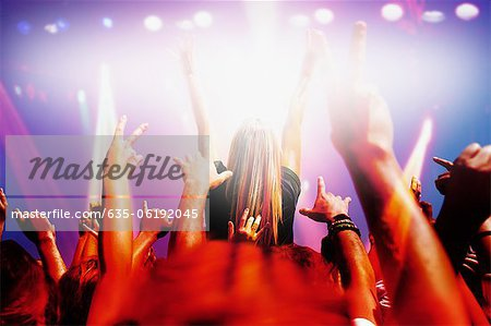 Stage lights shining on audience with arms raised at music concert Stock Photo - Premium Royalty-Free, Image code: 635-06192045