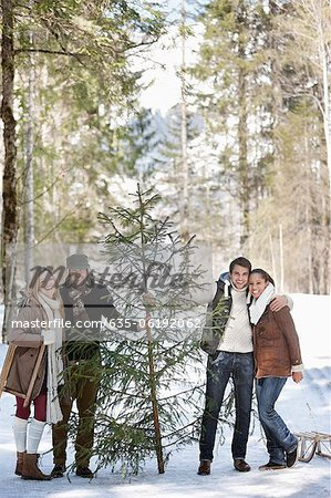Portrait of smiling couples with fresh cut Christmas tree in woods Stock Photo - Premium Royalty-Free, Image code: 635-06192062