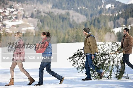 Couples and dog carrying fresh cut Christmas tree and gifts in snow Stock Photo - Premium Royalty-Free, Image code: 635-06192110
