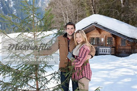 Portrait of smiling couple with fresh cut Christmas tree in front of cabin Stock Photo - Premium Royalty-Free, Image code: 635-06192138