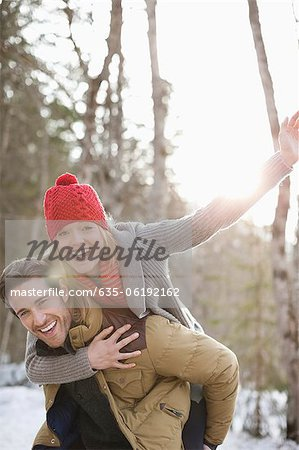 Portrait of smiling couple piggybacking in snow Stock Photo - Premium Royalty-Free, Image code: 635-06192162