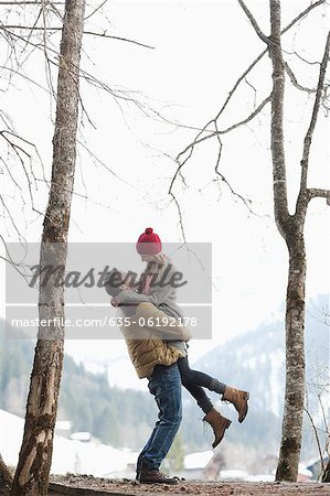 Man lifting woman in snowy woods Stock Photo - Premium Royalty-Free, Image code: 635-06192178