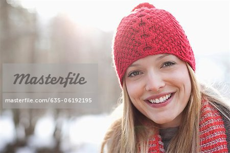 Close up portrait of smiling woman wearing red knit hat
