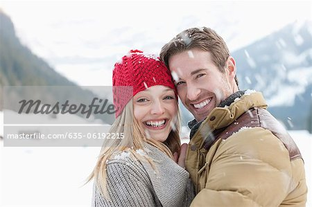 Portrait of smiling couple hugging in snow Stock Photo - Premium Royalty-Free, Image code: 635-06192215