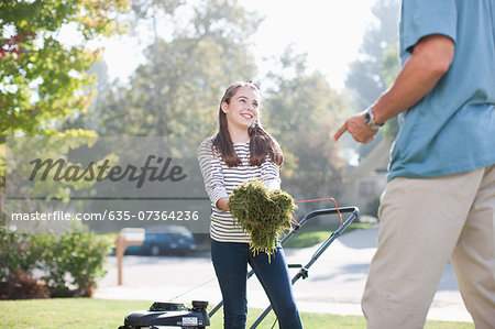 Father and daughter mowing lawn together Stock Photo - Premium Royalty-Free, Image code: 635-07364236