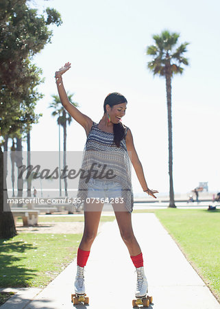 Smiling woman skating in park Stock Photo - Premium Royalty-Free, Image code: 635-07364283