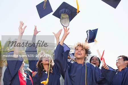Graduates tossing caps into the air Stock Photo - Premium Royalty-Free, Image code: 635-07364551