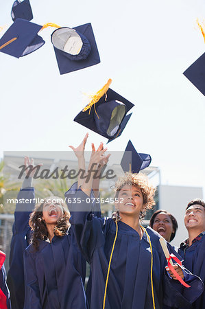 Graduates tossing caps into the air Stock Photo - Premium Royalty-Free, Image code: 635-07364552