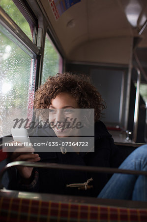 Smiling woman using cell phone on bus Stock Photo - Premium Royalty-Free, Image code: 635-07364722