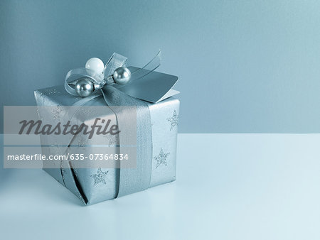 Christmas gift with silver ribbon and wrapping Stock Photo - Premium Royalty-Free, Image code: 635-07364834