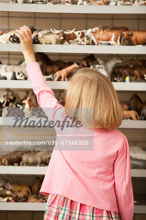 Girl reaching for plastic pig in toy store