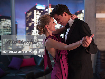 Elegant couple dancing in living room Stock Photo - Premium Royalty-Free, Image code: 635-07365384