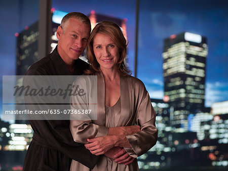 Couple in bathrobes hugging with city lights in background Stock Photo - Premium Royalty-Free, Image code: 635-07365387