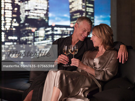 Couple in bathrobes drinking wine in living room at night Stock Photo - Premium Royalty-Free, Image code: 635-07365388