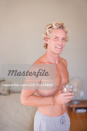 Man drinking glass of water at home Stock Photo - Premium Royalty-Free, Image code: 635-07456864