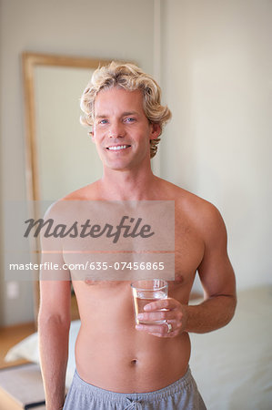 Man drinking glass of water at home Stock Photo - Premium Royalty-Free, Image code: 635-07456865