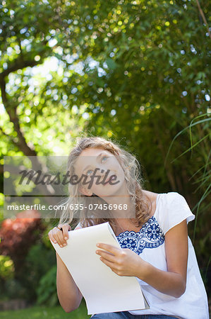 Girl sitting in grass and looking up with holding sketch pad Stock Photo - Premium Royalty-Free, Image code: 635-07456968