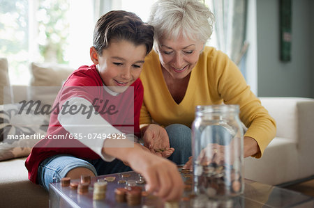 Grandmother and grandson counting coins Stock Photo - Premium Royalty-Free, Image code: 635-07494925
