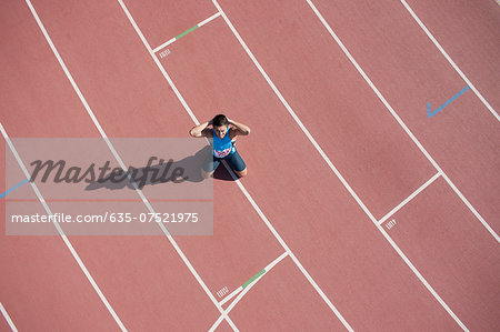 Disappointed runner kneeling on track Stock Photo - Premium Royalty-Free, Image code: 635-07521975