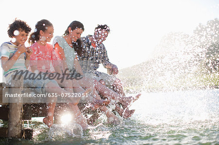 Family on dock splashing feet in lake Stock Photo - Premium Royalty-Free, Image code: 635-07522051
