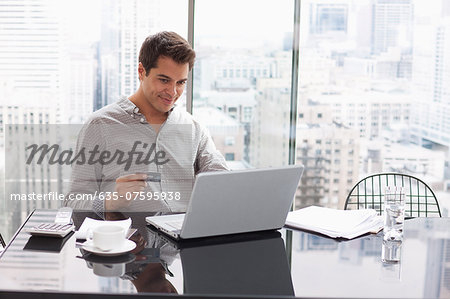 Businessman shopping online with credit card Stock Photo - Premium Royalty-Free, Image code: 635-07595938