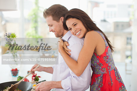 Woman hugging husband while he's cooking in kitchen Stock Photo - Premium Royalty-Free, Image code: 635-07595950