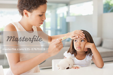 Mother taking daughter's temperature Stock Photo - Premium Royalty-Free, Image code: 635-07670815