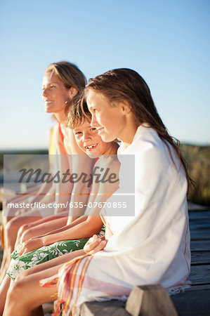 Family sitting on pier near beach Stock Photo - Premium Royalty-Free, Image code: 635-07670855