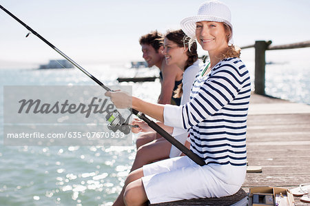 Friends fishing off pier at ocean Stock Photo - Premium Royalty-Free, Image code: 635-07670939
