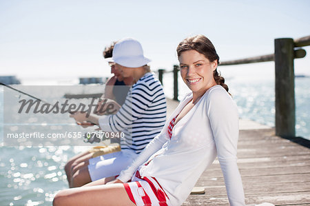 Friends fishing off pier at ocean Stock Photo - Premium Royalty-Free, Image code: 635-07670940