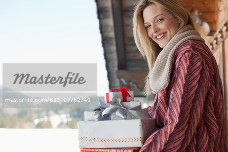 Portrait of smiling woman with Christmas gifts Stock Photo - Premium Royalty-Free, Image code: 635-07762740