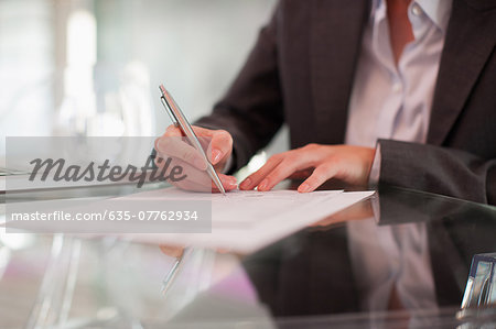 Businesswoman writing on paper at desk Stock Photo - Premium Royalty-Free, Image code: 635-07762934