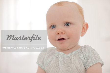 Smiling baby sitting on floor Stock Photo - Premium Royalty-Free, Image code: 635-07763063