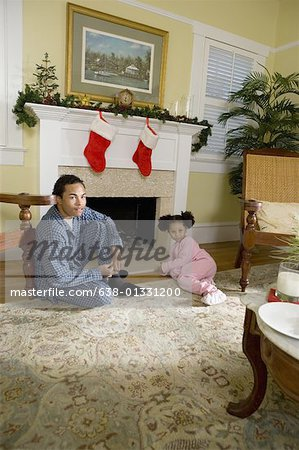 View of brother and sister sitting by fireplace decorated for Christmas, waiting for Santa Stock Photo - Premium Royalty-Free, Image code: 638-01331200