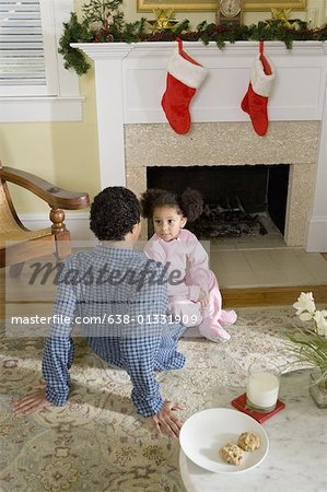 View of brother and sister sitting by fireplace decorated for Christmas, waiting for Santa Stock Photo - Premium Royalty-Free, Image code: 638-01331909