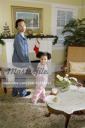 View of brother and sister standing by fireplace decorated for Christmas, waiting for Santa Stock Photo - Premium Royalty-Free, Image code: 638-01333363