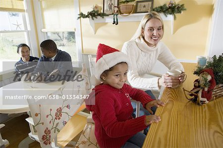 An inter-racial family sitting at the kitchen counter and table Stock Photo - Premium Royalty-Free, Image code: 638-01334347