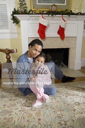 View of brother and sister sitting by fireplace decorated for Christmas, waiting for Santa Stock Photo - Premium Royalty-Free, Image code: 638-01334397