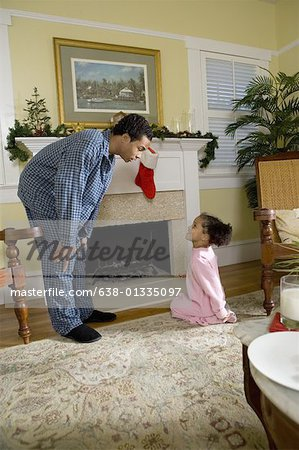 View of brother and sister by fireplace decorated for Christmas waiting for Santa Stock Photo - Premium Royalty-Free, Image code: 638-01335097