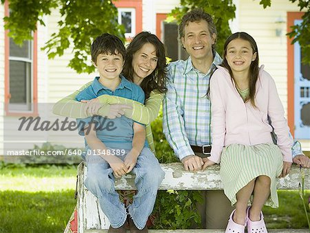 Portrait of a man and a woman smiling with their children Stock Photo - Premium Royalty-Free, Image code: 640-01348389