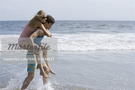 Profile of a young man carrying a young woman on his back Stock Photo - Premium Royalty-Free, Image code: 640-01348517