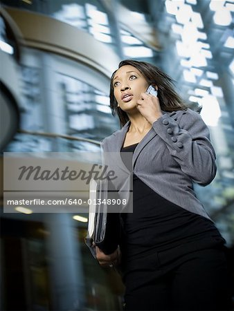 Businesswoman using a mobile phone and carrying files Stock Photo - Premium Royalty-Free, Image code: 640-01348908