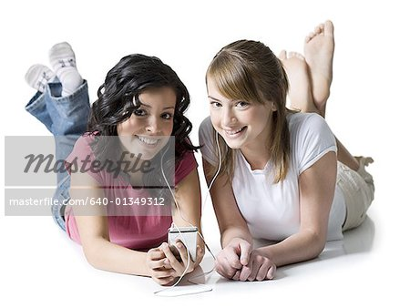 Portrait of two girls listening to music on an MP3 player Stock Photo - Premium Royalty-Free, Image code: 640-01349312
