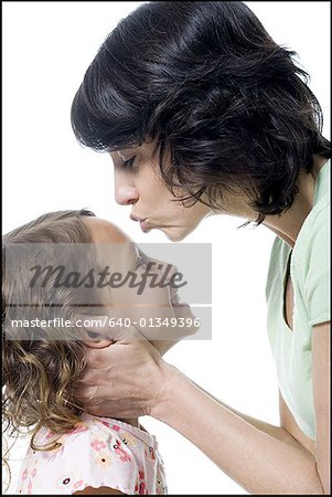 Close-up of a mid adult woman kissing her daughter's forehead Stock Photo - Premium Royalty-Free, Image code: 640-01349396