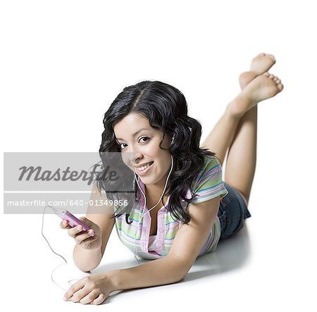 Portrait of a teenage girl listening to an Mp3 player Stock Photo - Premium Royalty-Free, Image code: 640-01349856
