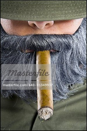 Close-up of a mid adult man smoking a cigar Stock Photo - Premium Royalty-Free, Image code: 640-01349937